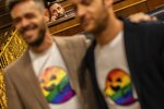 Socialist lawmakers dressed with a t-shirt bearing an emoji with the rainbow flag pose for the media in front far right Vox party leader Santiago Abascal, background, at the Spanish parliament in Madrid, Spain, Tuesday, May 21, 2019. The icon has become popular and has been dubbed as