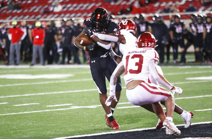 Texas Tech wide receiver Ja'Lynn Polk scores a touchdown, avoiding a tackle by Oklahoma cornerback Jaden Davis in the second half of an NCAA college football game Saturday, Oct. 31, 2020, in Lubbock, Texas. (AP Photo/Mark Rogers)