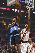 Cleveland Cavaliers guard Collin Sexton, left, shoots as Los Angeles Clippers forward Maurice Harkless, center, defends while forward Kawhi Leonard watches during the first half of an NBA basketball game Tuesday, Jan. 14, 2020, in Los Angeles. (AP Photo/Mark J. Terrill)