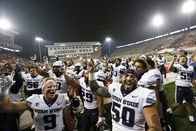 Utah State players sing the school's song while celebrating with fans after winning 26-23 against Washington State in an NCAA college football game, Saturday, Sept. 4, 2021, in Pullman, Wash. (AP Photo/Young Kwak)