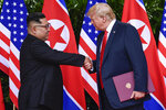 FILE - In this June 12, 2018, file photo, North Korea leader Kim Jong Un, left, and U.S. President Donald Trump shake hands at the conclusion of their meetings at the Capella resort on Sentosa Island in Singapore. When Trump and Kim first met in Singapore in 2018, there was pomp, there was circumstance, but there wasn't much substance. As they get ready to sit down again in Vietnam on Feb. 27-28, 2019,  there's growing pressure that they forge a deal that puts them closer to ending the North Korean nuclear weapons threat (AP Photo/Susan Walsh, Pool, File)