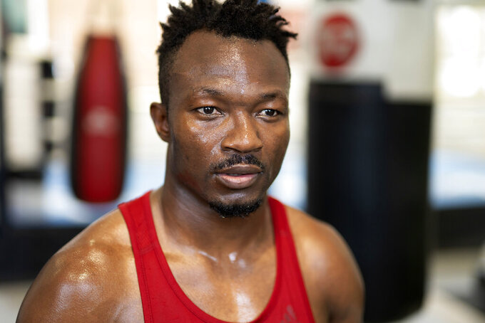 Boxer Thomas Essomba poses for a portrait after training at Steel City Gym in Sheffield, England, Thursday, Aug. 4, 2021. Cameroonian boxer Thomas Essomba, was one of seven people who defected at London 2012. Nine years on, he talks to AP about what it's been like to live with that decision. (AP Photo/Jon Super)