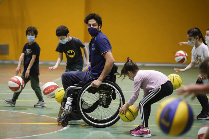 Adolfo Damian Berdun, of Argentina, a professional player and captain of the Argentine basketball Paralympic team, teaches children basketball at a primary school in Verano Brianza, on the outskirts of Milan, Italy, Tuesday, May 11, 2021. Four second-grade classes in the Milan suburb of Verano Brianza have been learning to play basketball this spring from a real pro. They also getting a lesson in diversity.  Their basketball coach for the last month has been Adolfo Damian Berdun, an Argentinian-Italian wheelchair basketball champion. Berdun, 39, lost his left leg in a traffic accident at ag 13 in his native Buenos Aires, and he has visited many schools over the years to discuss how he has lived with his disability. (AP Photo/Luca Bruno)