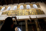 In this Thursday, Dec. 6, 2018 photo, a visitor photographs a renovated part of a fresco inside the Church of the Nativity, built atop the site where Christians believe Jesus Christ was born, in the West Bank City of Bethlehem. City officials are optimistic that the renovated church will help add to a recent tourism boom and give a boost to the shrinking local Christian population. (AP Photo/Majdi Mohammed)