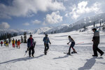 """Tourists ski down a slop in Afarwat, Gulmarg, northwest of Srinagar, Indian controlled Kashmir, Sunday, Jan. 10, 2021. Snow this winter has brought along with it thousands of locals and tourists to Indian-controlled Kashmir's high plateau, pastoral Gulmarg, which translates as """"meadow of flowers."""