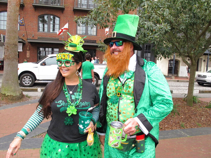 Shanna and Tyson Campbell sip drinks in their St. Patrick's Day costumes as they celebrate in Savannah, Ga., on Wednesday, March 17, 2021. Even with the city's 197-year-old parade canceled, Savannah saw a large number of tourists return for the Irish holiday. Some city officials worried the celebration could cause a coronavirus outbreak. (AP Photo/Russ Bynum)