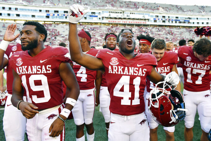 Arkansas players Tyson Morris (19) and T.J. Hammonds (41) celebrate their win over Georgia Southern after an NCAA college football game Saturday, Sept. 18, 2021, in Fayetteville, Ark. (AP Photo/Michael Woods)