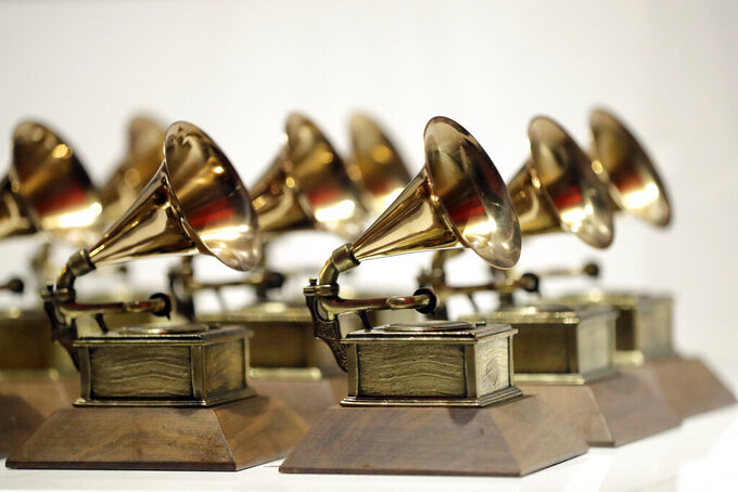 "FILE - In this Oct. 10, 2017, file photo, various Grammy Awards are displayed at the Grammy Museum Experience at Prudential Center in Newark, N.J. The Recording Academy is partnering with Berklee College of Music and Arizona State University to complete a study focused on women's representation in the music industry.. The academy, which puts on the annual Grammy Awards, said the lack of female creators in music is ""one of the most urgent issues in the industry today."" (AP Photo/Julio Cortez, File)"