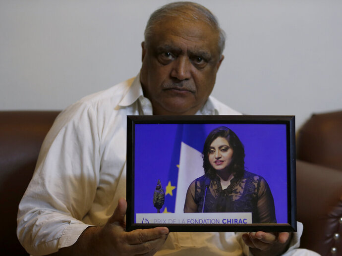 Professor Mohammad Ismail, father of a Pakistani human rights activist Gulalai Ismail, holds a picture of his daughter as he poses for a photo, in his home in Islamabad, Pakistan, Thursday, Oct. 17, 2019. A dozen plainclothes Pakistani security forces attempted to raid the former home of Gulalai Ismaila who recently fled to the United States seeking asylum. Gulalai's elderly parents say they were ordered to come outside