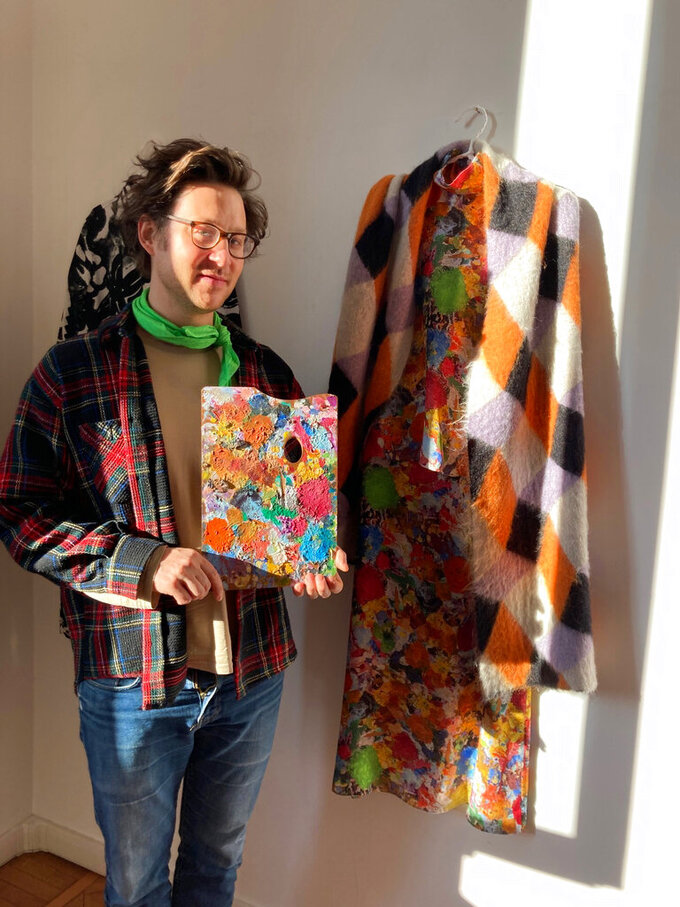 Milan-based Austrian fashion designer Arthur Arbesser, poses in his studio holding a painter's pallet that he picked up at a flea market, and which inspired the signature print for his Fall 2021 collection of 25 looks, in Milan, Italy, Sunday, Feb. 28, 2021. Arbesser decided against a runway show in this digital era, instead focusing his creative energies to make a collection from revitalized textiles from his archives that he had printed over, and experimenting with other artisanal techniques with his small team. (AP Photo/Colleen Barry)