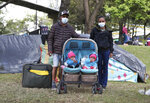 """Darwin Herrera, left, and his wife Jennifer Repelo pose with their six-month-old twins and luggage outside their tent in a park where they have been living since the end of May with other jobless Venezuelan migrants near the bus station in Bogota, Colombia, Wednesday, June 10, 2020. From Venezuela's Carabobo state, the former construction and courier migrated to Bogota two years ago, where Herrera found work unloading and loading trucks. The economic lockdown to contain the COVID-19 pandemic left Herrera without a job, and unable to pay rent, so the couple is looking to return home but doesn't have money for transportation, and long-distance travel within Colobmia is restricted. """"I want to get back to Venezuela because I don't want this life for our twins,"""" said Herrera. (AP Photo/Fernando Vergara)"""