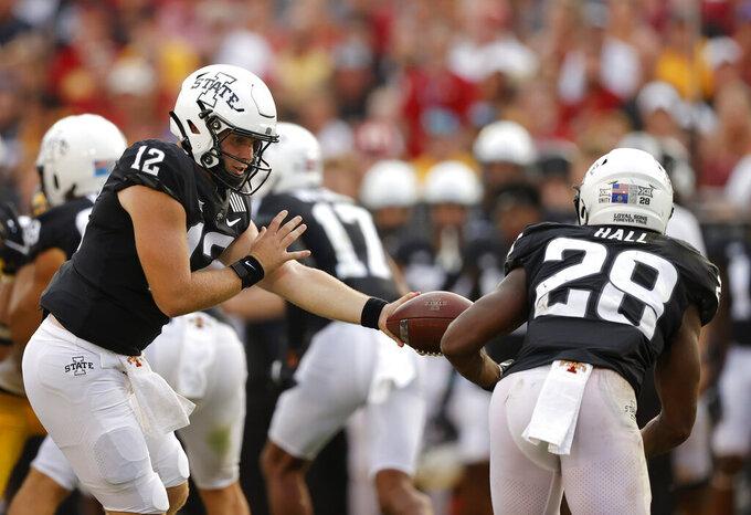 Iowa State quarterback Hunter Dekkers (12) hand off to running back Breece Hall (28) during the second half of an NCAA college football game against Iowa, Saturday, Sept. 11, 2021, in Ames, Iowa. Iowa won 27-17. (AP Photo/Matthew Putney)