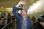 Chinese dissident writer Ma Jian waves to media after arriving Hong Kong international airport, Friday, Nov. 9, 2018. Despite Mallet's rejection, Hong Kong on Friday permitted dissident writer Ma to enter to attend a literary festival, even after an arts venue in the city canceled his appearance. Ma, whose novels frequently satirize China's communist leaders, told reporters he experienced nothing unusual while passing through passport control and that organizers were still lining-up a place for him to speak.