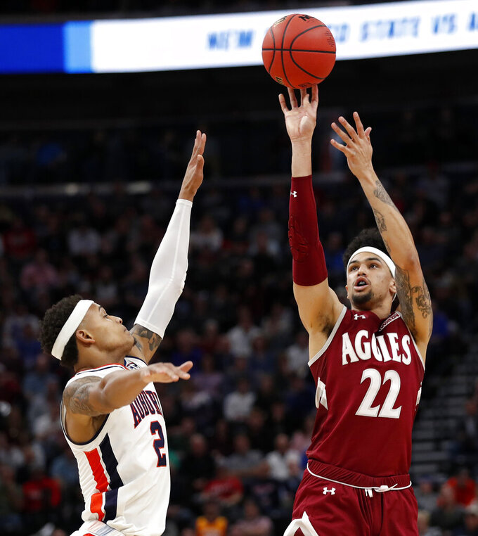 New Mexico State forward Eli Chuha (22) shoots over Auburn's guard Bryce Brown (2) during the first half in a first round men's college basketball game of the NCAA Tournament, Thursday, March 21, 2019, in Salt Lake City. (AP Photo/Jeff Swinger)