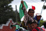 Central American migrants making their way to the U.S. in a large caravan wave a Mexican flag as they arrive to Tapachula, Mexico, after a truck driver gave them a free ride, Sunday, Oct. 21, 2018. Despite Mexican efforts to stop them at the Guatemala-Mexico border, about 5,000 Central American migrants resumed their advance toward the U.S. border Sunday in southern Mexico. (AP Photo/Moises Castillo)