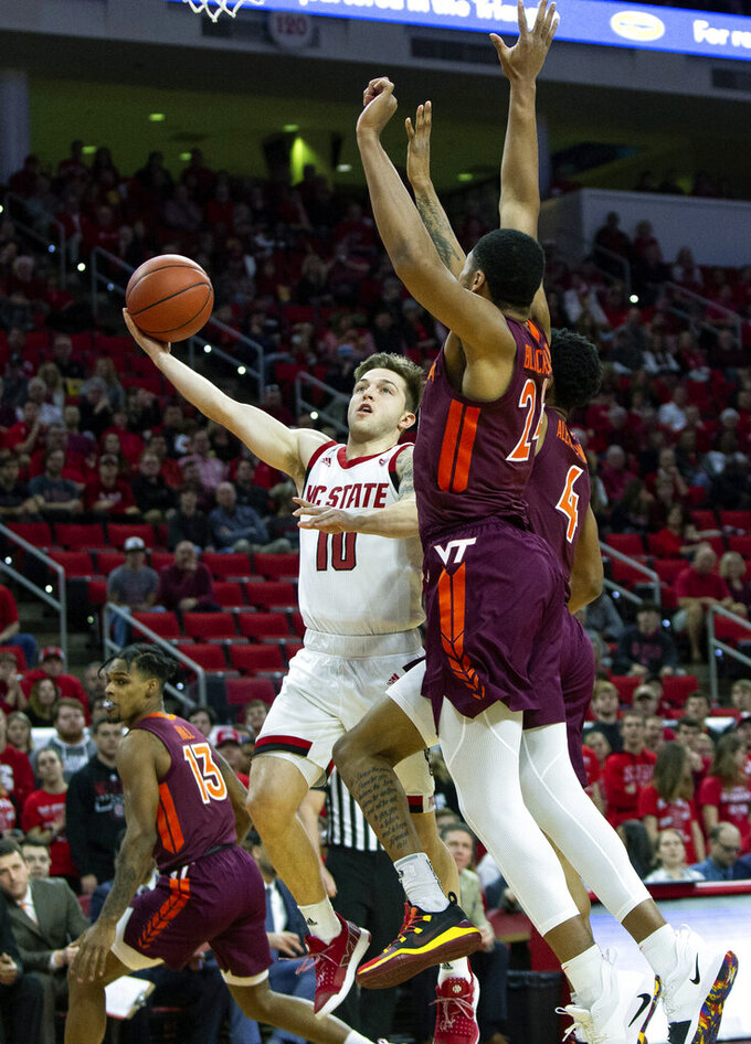 North Carolina State's Braxton Beverly (10) attempts a shot over Virginia Tech's Kerry Blackshear Jr. (24) and Virginia Tech's Nickeil Alexander-Walker (4) during the first half of an NCAA college basketball game in Raleigh, N.C., Saturday, Feb. 2, 2019. (AP Photo/Ben McKeown)