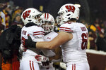 Wisconsin wide receiver Kendric Pryor, left, celebrates with teammates running back Jonathan Taylor, center, and offensive lineman Logan Bruss, right, after Pryor scored a touchdown against Minnesota during an NCAA college football game Saturday, Nov. 30, 2019, in Minneapolis. Wisconsin won 38-17. (AP Photo/Stacy Bengs)