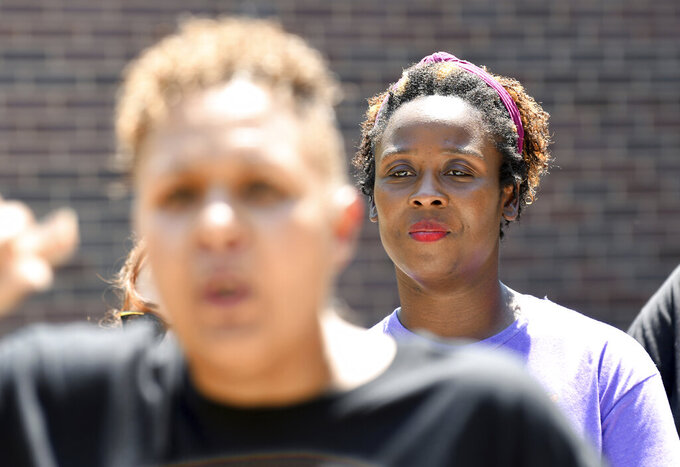 Community activist Shenika Carter, background, listens to Candice Bailey speak during a news conference in Aurora, Colo., on Wednesday, July 28, 2021. Local activists and former members of Aurora's community police task force gathered to call attention to police brutality. Aurora police announced Monday that an officer was arrested after video showed him using his pistol to beat a man he was trying to take into custody, choking him and threatening to kill him, while another officer was accused of failing to stop her colleague. (AP Photo/Thomas Peipert)