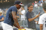 New York Yankees' relief pitcher Aroldis Chapman, left, admires a photo taken by a young fan, center, after working out before a baseball game between the Yankees and the Tampa Bay Rays was postponed due to severe weather in the area, Wednesday, July 17, 2019, in New York. (AP Photo/Kathy Willens)