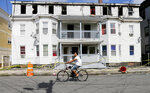 A man on a bicycle rides past a house destroyed by fire on Springfield St in Lawrence, Mass., Friday, Sept. 14, 2018. Multiple houses were damaged Thursday afternoon from gas explosions and fires triggered by a problem with a gas line that feeds homes in several communities north of Boston. (AP Photo/(AP Photo/Mary Schwalm)