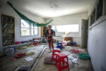 A woman looks at the damage caused by a rocket fired from Gaza that hit a house in a moshav in Israel near the border with Gaza, Saturday, May 4, 2019. Palestinian militants in the Gaza Strip fired at least 90 rockets into southern Israel on Saturday, according to the Israeli military, triggering retaliatory airstrikes and tank fire against militant targets in the blockaded enclave and shattering a month-long lull in violence. (AP Photo/Tsafrir Abayov)