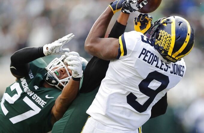 Michigan State safeties Xavier Henderson and Khari Willis (27) break up a pass intended for Michigan wide receiver Donovan Peoples-Jones (9) during the first half of an NCAA college football game, Saturday, Oct. 20, 2018, in East Lansing, Mich. (AP Photo/Carlos Osorio)