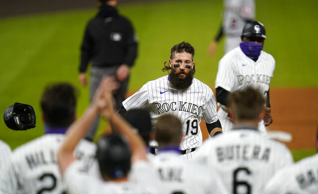 Colorado Rockies' Charlie Blackmon nears home and waiting teammates after hitting a grand slam off Los Angeles Angels relief pitcher Jose Quijada during the ninth inning of a baseball game Friday, Sept. 11, 2020, in Denver. The Rockies won 8-4. (AP Photo/David Zalubowski)