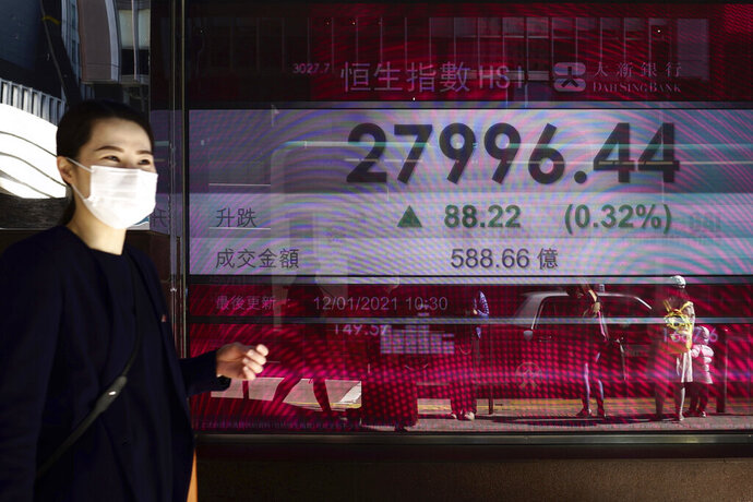 A woman walks past a bank's electronic board showing the Hong Kong share index at Hong Kong Stock Exchange in Hong Kong Tuesday, Jan. 12, 2021. Asian stocks advanced Tuesday as investors watched for details of U.S. President-elect Joe Biden's promised economic stimulus plan. (AP Photo/Vincent Yu)