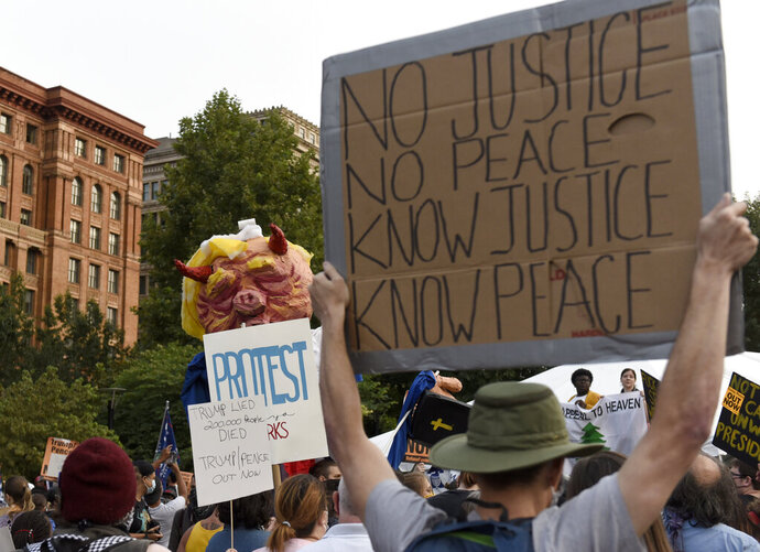 People gather at Independence Mall to protest U.S. President Donald Trump as he visits the National Constitution Center to participate in the ABC News town hall, Tuesday, Sept. 15, 2020, in Philadelphia. (AP Photo/Michael Perez)
