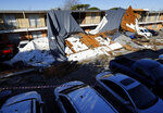 The roof of a Waterdance Apartments building was peeled off by a tornado-warned storm Tuesday night and landed on residents cars in the parking lot. Damage also occurred at The Mirage Apartments along Pioneer Parkway in Arlington, Texas Wednesday, Nov. 25, 2020. (Tom Fox/The Dallas Morning News via AP)