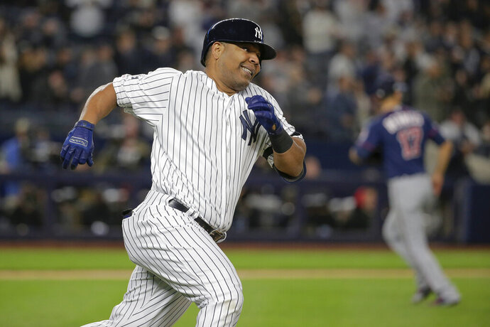 FILE - In this Oct. 4, 2019, file photo, New York Yankees designated hitter Edwin Encarnación runs down the first base line after hitting a double against the Minnesota Twins during the first inning of Game 1 of a baseball American League Division Series in New York. The Chicago White Sox have agreed to a $12 million, one-year contract with veteran slugger Encarnación, a person familiar with the negotiations told The Associated Press on Wednesday night. The person spoke on condition of anonymity because the deal has not been announced. Encarnación is due $11 million in salary next season and a $1 million signing bonus, with the White Sox holding an option for the 2021 season. (AP Photo/Seth Wenig, File)