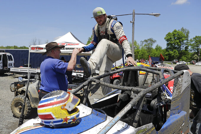 Cole Ketchum climbs into his car before a practice session at Gas City I-69 Speedway, Sunday, May 24, 2020, in Gas City, Ind. (AP Photo/Darron Cummings)