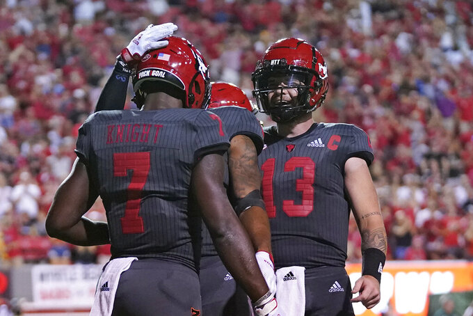 North Carolina State running back Zonovan Knight (7) and quarterback Devin Leary (13) react following Knight's touchdown against South Florida during the second half of an NCAA college football game in Raleigh, N.C., Thursday, Sept. 2, 2021. (AP Photo/Gerry Broome)