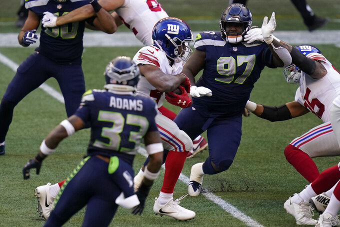 New York Giants running back Alfred Morris, center-left, gets past Seattle Seahawks Seattle Seahawks defensive tackle Poona Ford (97) to rush for a touchdown during the second half of an NFL football game, Sunday, Dec. 6, 2020, in Seattle. (AP Photo/Elaine Thompson)