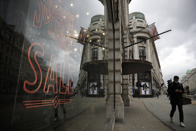 FILE - In this Friday, March 26, 2021 file photo, a person walks past a temporarily closed clothes shop on Regent Street in central London, where non-essential shops are closed during England's third coronavirus lockdown. The British economy contracted by 1.5% in the first quarter of 2021, a relatively modest contraction given that the country was in the midst of a strict lockdown to combat a second wave of the coronavirus. The Office for National Statistics also said Wednesday May 12, 2021, that the economy even managed to grow by 2.1% in March when the country began easing some restrictions. (AP Photo/Matt Dunham, File)