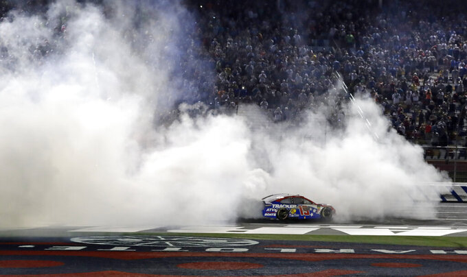 Martin Truex Jr. celebrates after winning the NASCAR Cup Series auto race at Charlotte Motor Speedway in Concord, N.C., Sunday, May 26, 2019. (AP Photo/Chuck Burton)