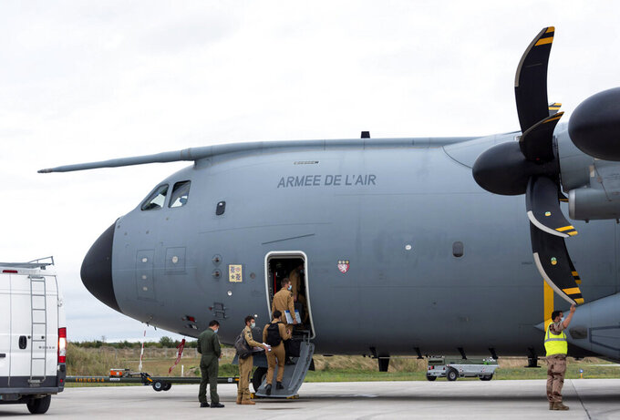 In this photo provided by the French Defense Ministry, French soldiers board a military Airbus A400M to evacuate French citizens from Afghanistan, Monday, Aug.16, 2021 in Orleans, central France. France is relocating its embassy in Kabul to the airport to evacuate all citizens still in Afghanistan, initially transferring them to Abu Dhabi. Evacuations have been in progress for weeks and a charter flight put in place by France in mid-July. (Etat-Major des Armees via AP)