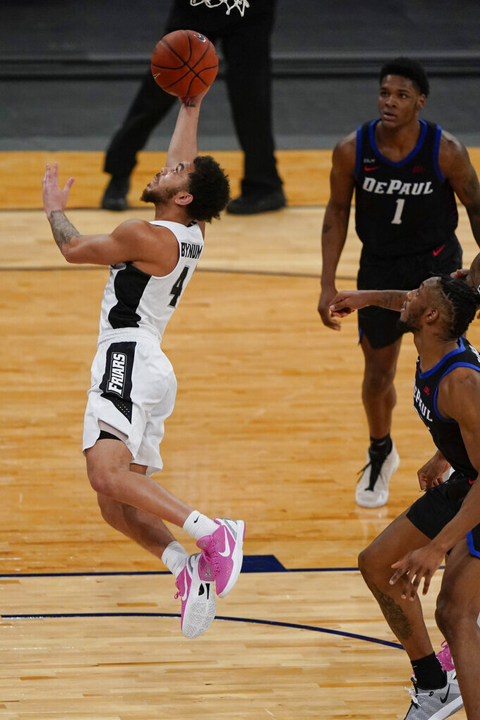 Providence's Jared Bynum (4) drives past DePaul's Romeo Weems (1) and Pauly Paulicap during the second half of an NCAA college basketball game in the Big East conference tournament Wednesday, March 10, 2021, in New York. (AP Photo/Frank Franklin II)
