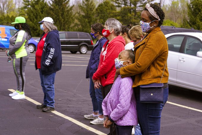 People gather for a prayer during a vigil at the Missionary Baptist Church in Indianapolis, Saturday, April 17, 2021 for the victims of the shooting at a FedEx facility. A gunman killed eight people and wounded several others before taking his own life in a late-night attack at a FedEx facility near the Indianapolis airport, police said. (AP Photo/Michael Conroy)