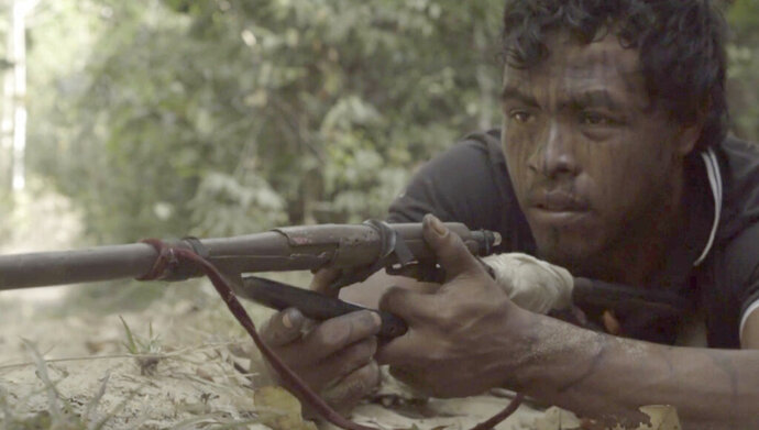 In this Sept. 2019, video frame, Paulo Paulino Guajajara, a Forest Guardian protecting the Arariboia indigenous reserve poses with his makeshift weapon, at the reserve in Maranhao state, Brazil. The 26-year-old Guajajara was killed in an ambush by illegal loggers on Friday, Nov. 1, 2019.