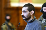 A Syrian man identified as Hassan F. arrives at the Metropolitan Court in Budapest, Hungary, Wednesday, Nov. 13, 2019. Prosecutors said the 27-year-old man identified only as Hassan F. participated in the beheading of a religious leader in the city of al-Sukhnah in Homs province and was also involved in the killings of at least 25 people. (Zsolt Szigetvary/MTI via AP)