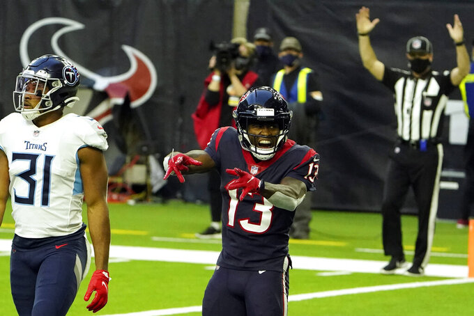 Houston Texans wide receiver Brandin Cooks (13) celebrates after catching a touchdown pass as Tennessee Titans free safety Kevin Byard (31) walks past during the second half of an NFL football game Sunday, Jan. 3, 2021, in Houston. (AP Photo/Eric Christian Smith)