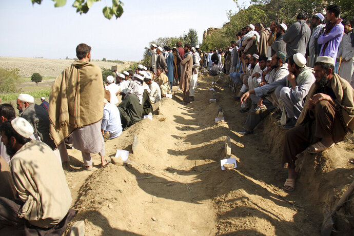 Afghan men bury victims of Friday's deadly bomb blast in the mosque in the village of Jodari at Haskamena district of Jalalabad east of Kabul, Afghanistan, Saturday, Oct. 19, 2019. Funerals are being held in eastern Afghanistan for the victims of Friday's deadly bomb blast in a village mosque which killed 62 people during prayers. (AP Photo/Wali Sabawoon)
