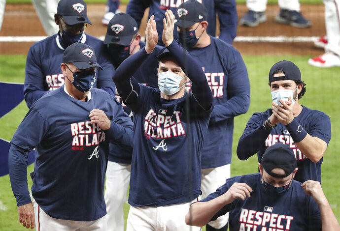 From left, Atlanta Braves manager Brian Snitker, Freddie Freeman, and Dansby Swanson celebrate clinching their third consecutive National League East championship title with a victory over the Miami Marlins in a baseball game on Tuesday, Sept. 22, 2020, in Atlanta. (Curtis Compton/Atlanta Journal-Constitution via AP)