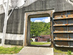 In this Tuesday, May 12, 2020, photo the town of Matewan, W.Va, is shown through a river floodwall gate. A gunfight between miners and detectives hired by a coal company on a Matewan street left 10 people dead on May 19, 1920. It became known as the Matewan Massacre. (AP Photo/John Raby)