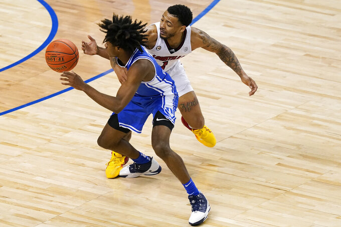 Duke guard DJ Steward, left, and Louisville guard Carlik Jones, right, battle for a rebound during the second half of an NCAA college basketball game in the second round of the Atlantic Coast Conference tournament in Greensboro, N.C., Wednesday, March 10, 2021. (AP Photo/Gerry Broome)