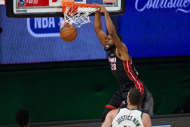 Miami Heat's Andre Iguodala (28) dunks in front of Milwaukee Bucks' Brook Lopez (11) in the second half of an NBA conference semifinal playoff basketball game Tuesday, Sept. 8, 2020 in Lake Buena Vista, Fla. (AP Photo/Mark J. Terrill)