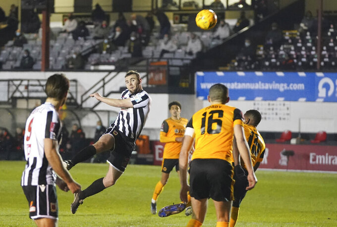 Chorley's Connor Hall, centre, heads the ball during the Emirates FA Cup fourth round soccer match between Chorley and Wolverhampton Wanderers at Victory Park in Chorley, England, Friday, Jan. 22, 2021. (AP Photo/Jon Super)