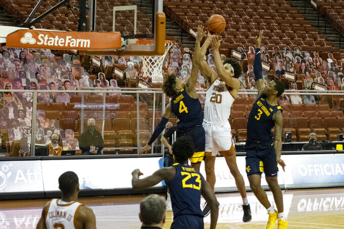 Texas forward Jericho Sims (20) attempts a buzzer-beater shot to tie the game late in the second half of an NCAA college basketball game against West Virginia guard Miles McBride (4) and forward Gabe Osabuohien (3), Saturday, Feb. 20, 2021, in Austin, Texas. Sims missed the shot and West Virginia won 84-82. (AP Photo/Michael Thomas)