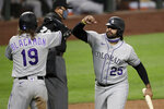 Colorado Rockies' Charlie Blackmon (19) and Matt Kemp (25) share congratulations after both scored against the Seattle Mariners in the sixth inning of a baseball game Friday, Aug. 7, 2020, in Seattle. (AP Photo/Elaine Thompson)